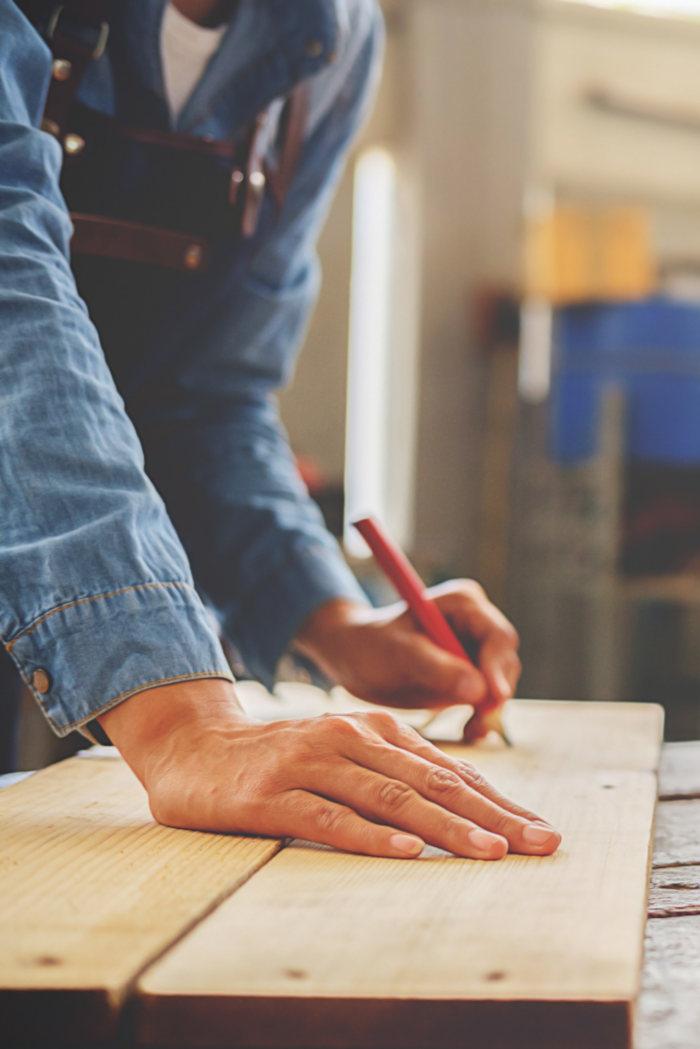 Snekker måler opp planken til oppussingsprosjektet