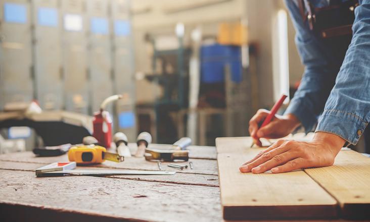 Mann som måler en planke